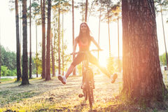 Woman riding bicycle with stretching her legs in the air. Stock Photo