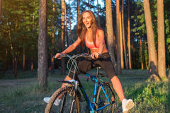 Woman riding bicycle with stretching her legs in the air. Royalty Free Stock Image
