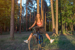 Woman riding bicycle with stretching her legs in the air. Royalty Free Stock Images