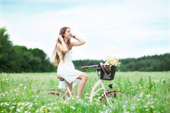 Woman riding bicycle in wildflower field Stock Images