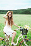 Woman riding bicycle in wildflower field Stock Photos