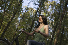 Woman Riding Bicycle In Woodland Stock Images