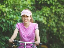 Woman riding bicycle. A young smiling woman with a cap riding a bicycle with foliage in the background royalty free stock image