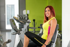 Woman riding bicycle. Young Women spinning in the gym, exercising her legs doing cardio training Royalty Free Stock Photo
