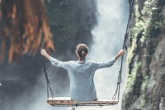 Woman Riding Big Swing in Front of Waterfalls royalty free stock images