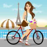 Woman riding a bike with a basket full of flowers Stock Images