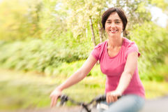 Woman riding bike on forest meadow. Royalty Free Stock Photos