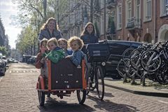 Family on bicycles in Amsterdam. Woman riding a bike four children on the Bakfiet on the street in Amsterdam, Netherlands royalty free stock photos
