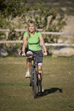 Woman riding bike on grass Royalty Free Stock Images
