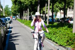 Woman riding a bike while making pictures Stock Photo