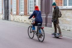 A woman riding bike and a man riding one wheel hoverboard on the road