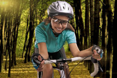 Woman riding a bike outside in forest Stock Images