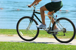 Woman riding a bike at the park by the lake Royalty Free Stock Image