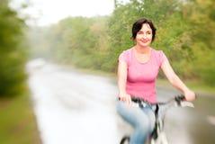 Woman riding bike on the rainy Stock Photos
