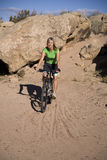 Woman riding bike in sand Stock Photo