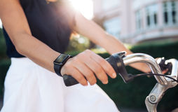 Woman riding bike with a smartwatch Royalty Free Stock Photography