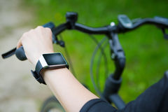 Woman riding a bike with a smartwatch heart rate monitor. Royalty Free Stock Images