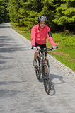 Woman riding bike on sunny cycling path Stock Images