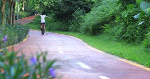 I can fly with my bike. Woman riding a bike on sunny park trail with arms outstretched stock video footage