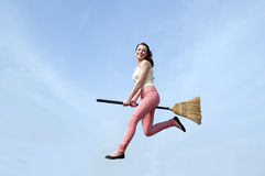 Woman riding broom Stock Image