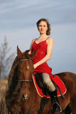 Woman riding brown horse Stock Photos
