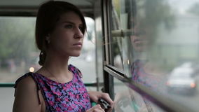 Woman riding in a bus and looking in window. Woman riding in a trolley and looking in window stock video