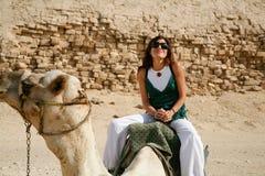 Woman riding camel Stock Images