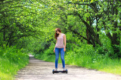 Woman riding an electrical scooter outdoors - hover board, smart balance wheel, gyro scooter, hyroscooter, personal Eco transport Royalty Free Stock Photos