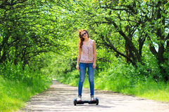 Woman riding an electrical scooter outdoors - hover board, smart balance wheel, gyro scooter, hyroscooter, personal Eco transport Stock Photography