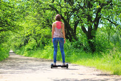 Woman riding an electrical scooter outdoors - hover board, smart balance wheel, gyro scooter, hyroscooter, personal Eco transport Stock Image