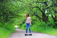 Woman riding an electrical scooter outdoors - hover board, smart balance wheel, gyro scooter, hyroscooter, personal Eco transport Stock Photos