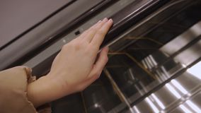 A woman is riding an escalator. Closeup of a hand holding a railing. A woman in a beige jacket riding an escalator. Close-up hands stock video