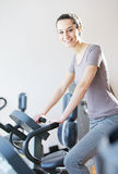 Woman riding an exercise bike Stock Photos