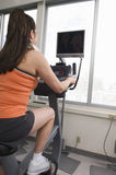 Woman Riding An Exercise Bike Stock Photography