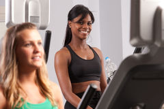 Woman riding exercise bike stock images