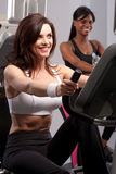 Woman riding exercise bike Stock Photo