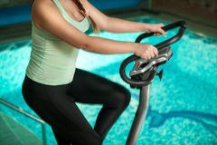Woman riding exercise bike against swimming pool Stock Images
