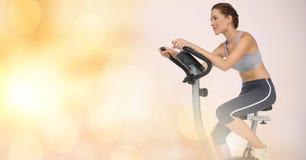Woman riding exercise bike Royalty Free Stock Photos