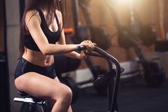 Woman riding an exercise bike in gym. fit girl doing cardio training on bicycle. Happy woman wearing black top riding an exercise bike in gym. fit girl doing Stock Images