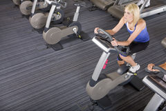 Woman riding exercise bike in health club Stock Photography
