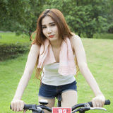 Woman riding an exercise bike in the park. Stock Photography