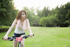 Woman riding an exercise bike in the park. Stock Photos