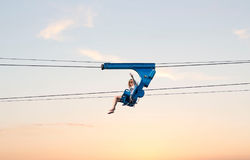 Woman riding high in the air on a zip line. stock photography