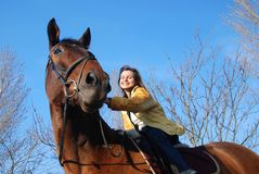Woman riding on horse. Young woman riding on big brown horse with blue sky in background Stock Photos