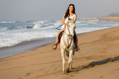 Woman riding horse beach. Beautiful young woman riding a horse on beach in early morning Royalty Free Stock Photos