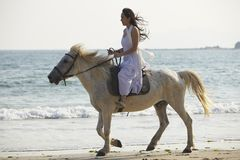 A woman riding horse on beach. A Chinese woman riding horse on beach Stock Photo