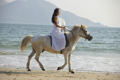 A woman riding horse on beach. A Chinese young woman riding horse on beach Royalty Free Stock Photography