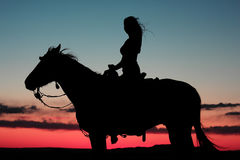 Woman Riding Horse in Brilliant Sunset. Silhouette of woman riding a horse in a beautiful desert sunset with a slight breeze blowing her hair Royalty Free Stock Photos