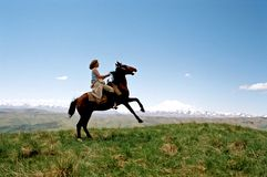 Woman riding horse in country. Side view of woman riding horse over field with snow capped Caucasus, mountains in background Stock Photo