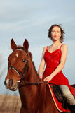 Woman riding horse in the field Stock Photo